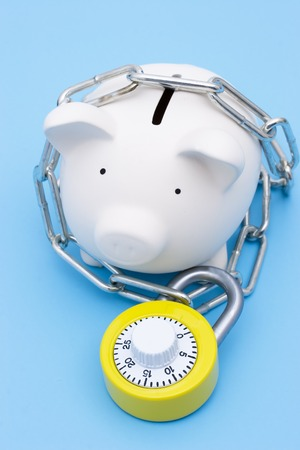 A piggy bank with chains and a bright yellow combination lock photo