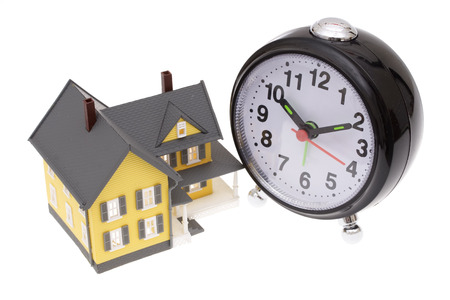 A bright yellow house with an alarm clock Stock Photo