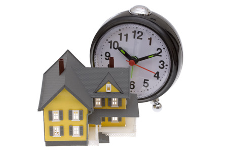 downpayment: A bright yellow house with an alarm clock Stock Photo