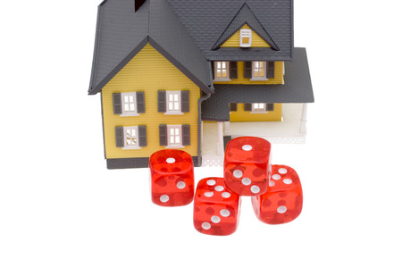 subprime: A bright yellow house with red dice Stock Photo