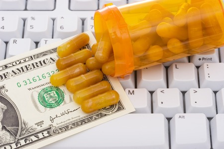 technology transaction: close-up of a computer white keyboard with pills and money - computerized healthcare Stock Photo