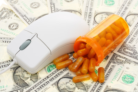 technology transaction: a computer mouse with pills and money background - computerized healthcare