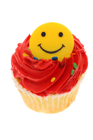 smiley: Delight colored cupcake on isolated on a white background with a smiley face