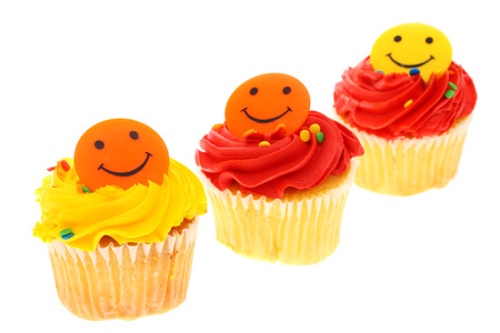 smiley: Delight colored cupcakes on isolated on a white background with a smiley face