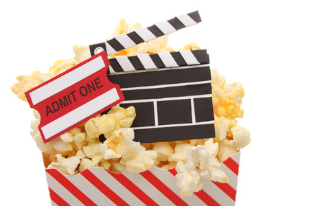 Popcorn with an admit ticket and movie clapper in a popcorn bag isolated on white background photo