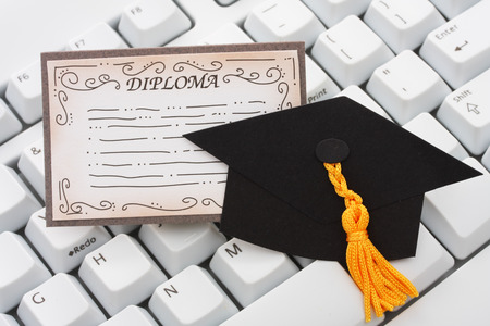 computer instruction:  A black graduation cap and diploma with a keyboard on an isolated background