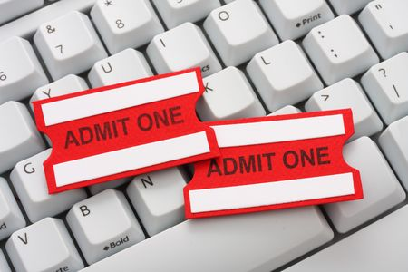 raffle ticket: Two red and white admit one tickets on a computer keyboard