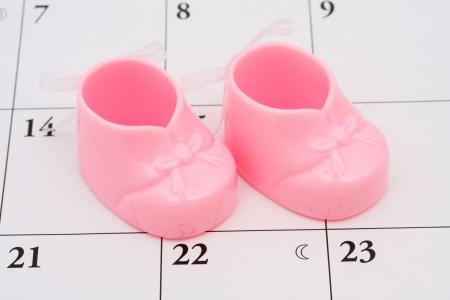 mother to be: Due scarpette rosa baby su un calendario  Archivio Fotografico