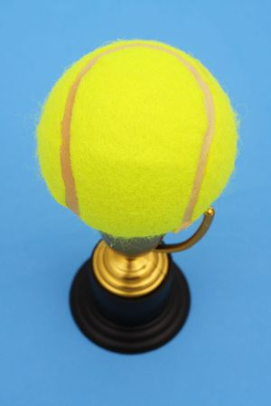 Gold trophy holding tennis ball on blue background photo