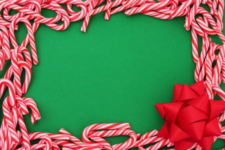 candy border: Mini candy canes as border with bow - christmas background