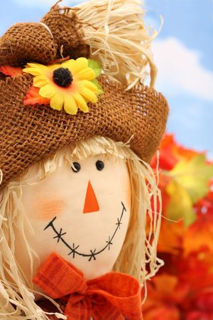 Scarecrow with fall leaves and sky background photo