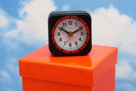 Clock sitting on gift box sky background photo