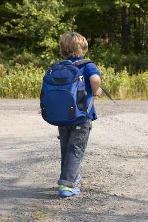 book bag: Young boy waiting for the bus