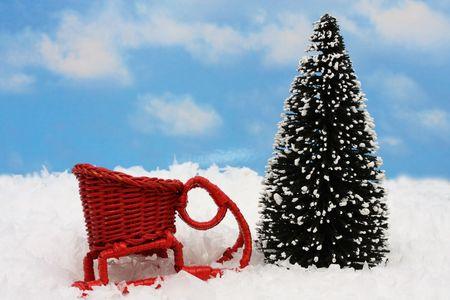 Red sleigh sitting on snow beside tree Фото со стока
