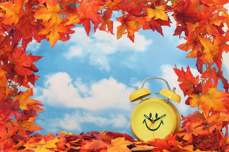 Fall leaf border with clock, sky background Stock Photo
