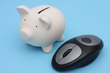 Piggy bank next to a computer mouse photo