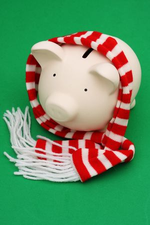 Piggy bank wearing striped scarf on green background photo
