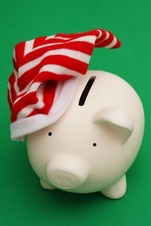 Christmas hat on piggy bank on a green background photo