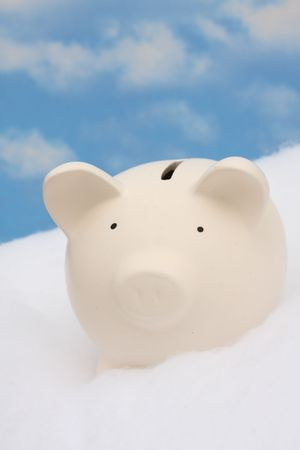 Piggy bank sitting on clouds, sky background