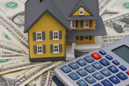 House and calculator sitting on American currency Stock Photo - 1888563