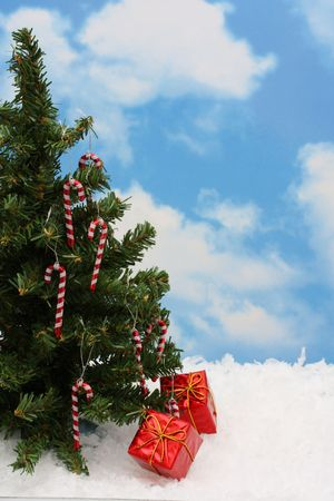 bight: Christmas tree with bight red presents under it and ablue sky background