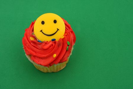 Cupcake with happy face on green background Stock Photo - 1907761