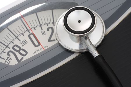 Close up of stethoscope on a weight scales