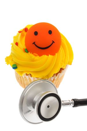 stethoscope: Close up of cupcake with stethoscope isolated on a white background