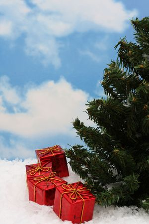 holiday spending: Christmas tree with four presents on snow