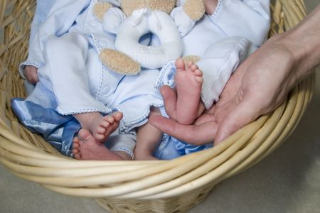 Baby feet with one being held up by daddy photo