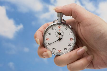 Stopwatch in hand with a sky background Imagens