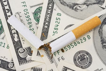 non: Broken cigarette on American five dollar bills