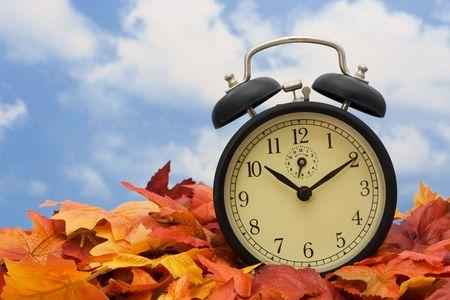 Retro clock on fall leaves sky background Stock Photo