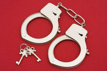 Handcuff with keys on red background Stock Photo - 2079067