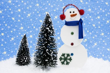 Snowman with trees on night sky background photo