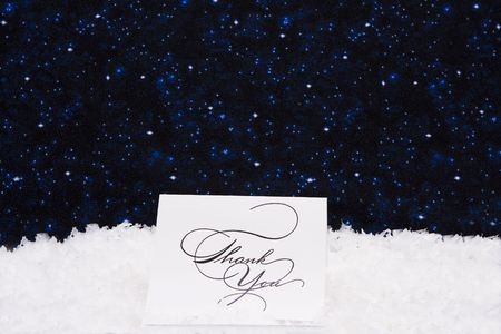 Thank you card sitting on snow with a night background photo