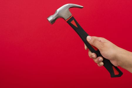 Hammer in hand on red background with copy space Stock Photo - 2454105