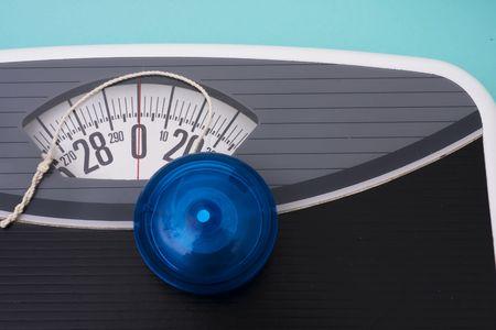 Blue yo-yo sitting on scales on blue background Stock Photo