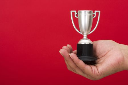 silver medal: Trophy in hand on red background with copy space Stock Photo