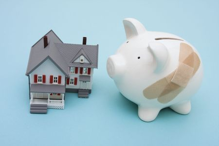 Piggy bank with adhesive bandage and house on blue background Stock Photo - 2463626