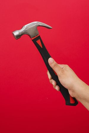 Hammer in hand on red background with copy space Stock Photo - 2463634
