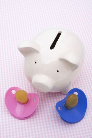 Piggy bank with pacifiers on pink background photo