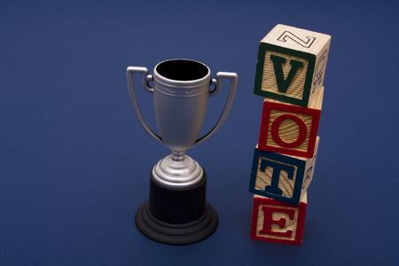 Trophy with vote alphabet blocks on a blue background Stock Photo - 2526009
