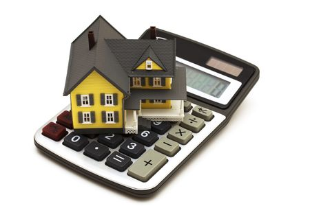 in escrow: House sitting on calculator isolated on white background