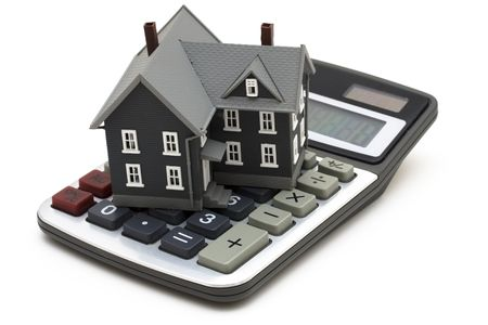 in escrow: House sitting on calculator isolated on white