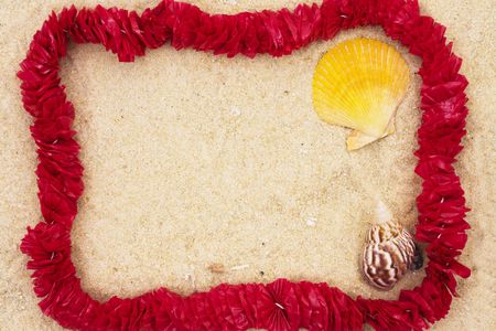 Lei on sand with shells with copy space in center photo