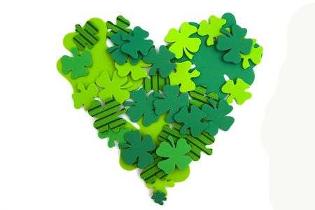 Four leaf clovers in heart shape isolated on white photo