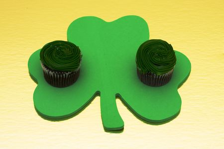 Shamrock with two chocolate cupcakes on a gold background Stock Photo - 2731912