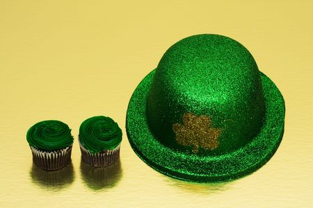 Shamrock hat with chocolate cupcakes on gold background photo
