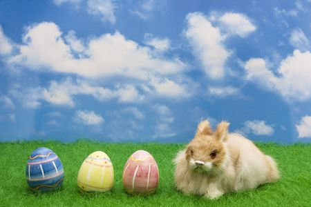 Easter bunny sitting on grass with Easter eggs